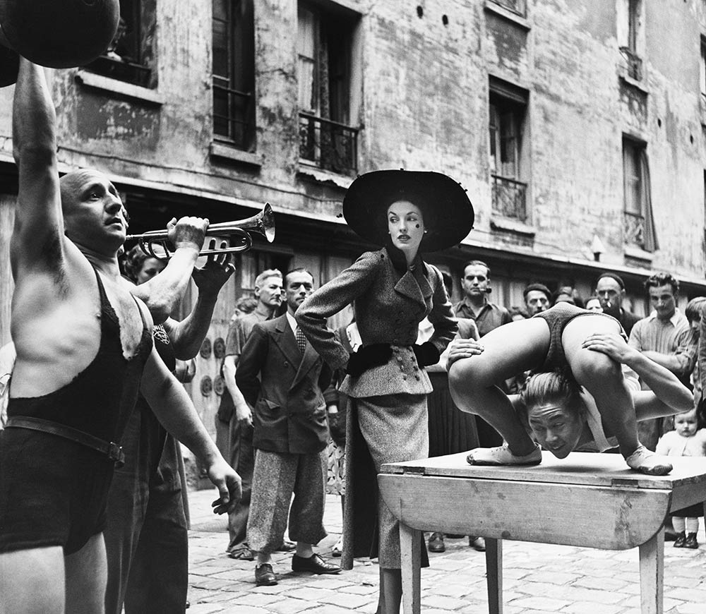 Elise Daniels with street performers, suit by Balenciaga, Le Marais, Paris, 1948 - © The Richard Avedon Foundation